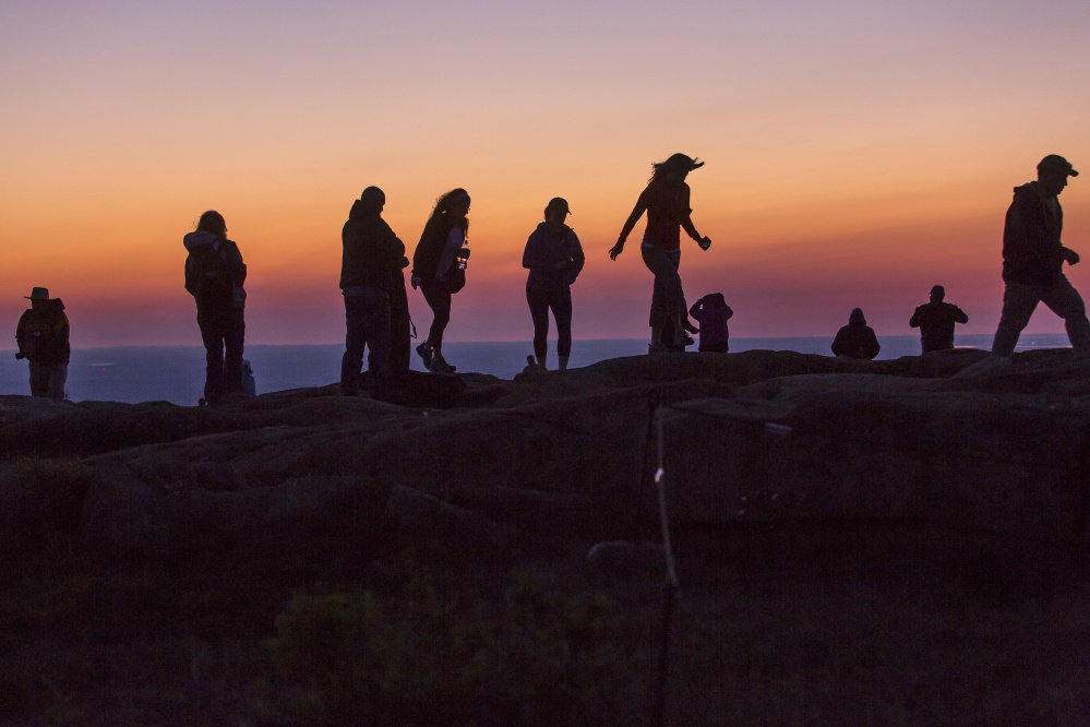 "Visitors amble along the summit of Cadillac Mountain at dawn Monday. Acadia has been attracting ever-increasing crowds that some fear will threaten to fundamentally alter the experience of the park's natural beauty. ""We don't want people stuck in traffic hunting endlessly for a place to park,"" said Kevin Schneider, park superintendent."