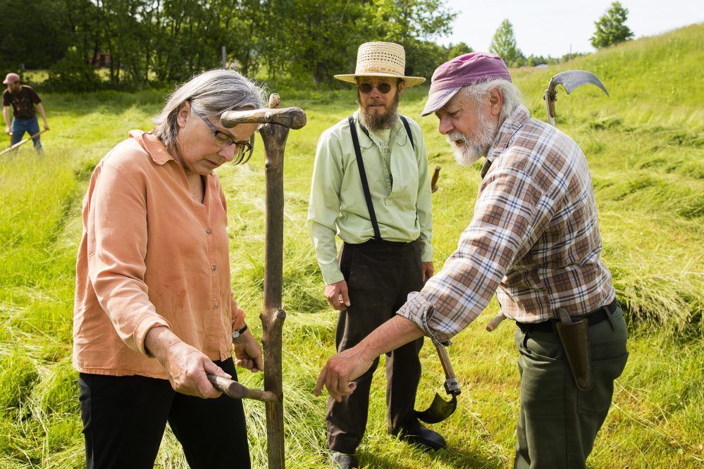 John McIntire of Unity, right, shows Terry Yarmoluk of Clinton, left, his Canadian-made scythe at the Common Ground Fairgrounds in Unity. Kenneth Copp of Thorndike looks on at center.