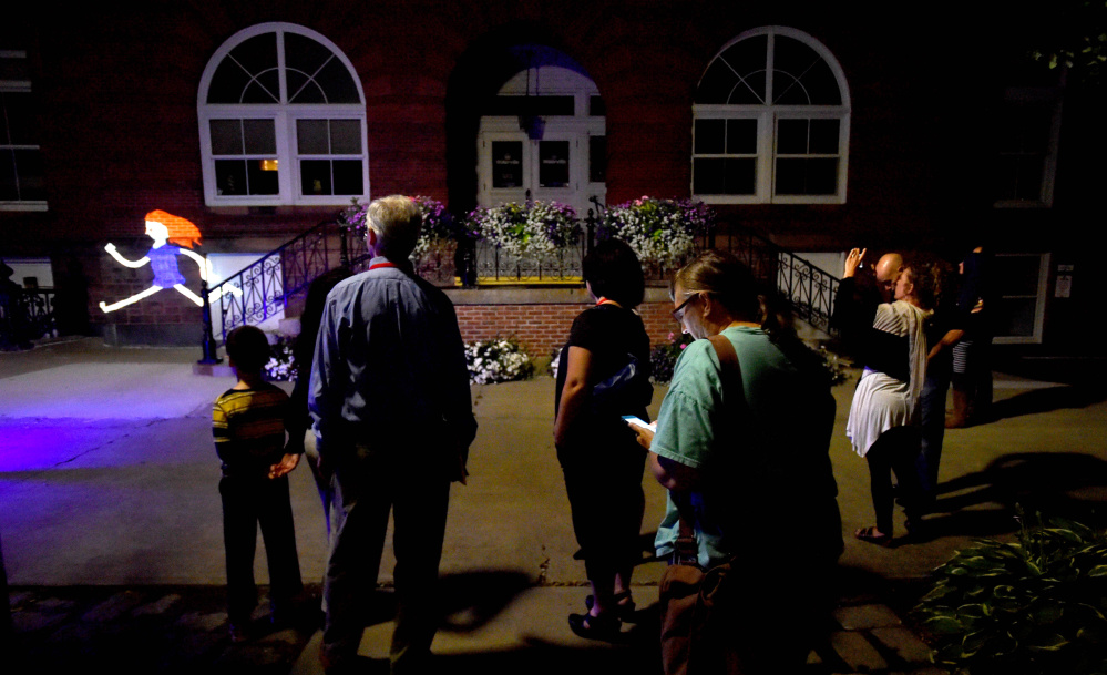Spectators watch the projected animated creations of VJ Sauve during a performance Friday at Castonguay Square in Waterville.