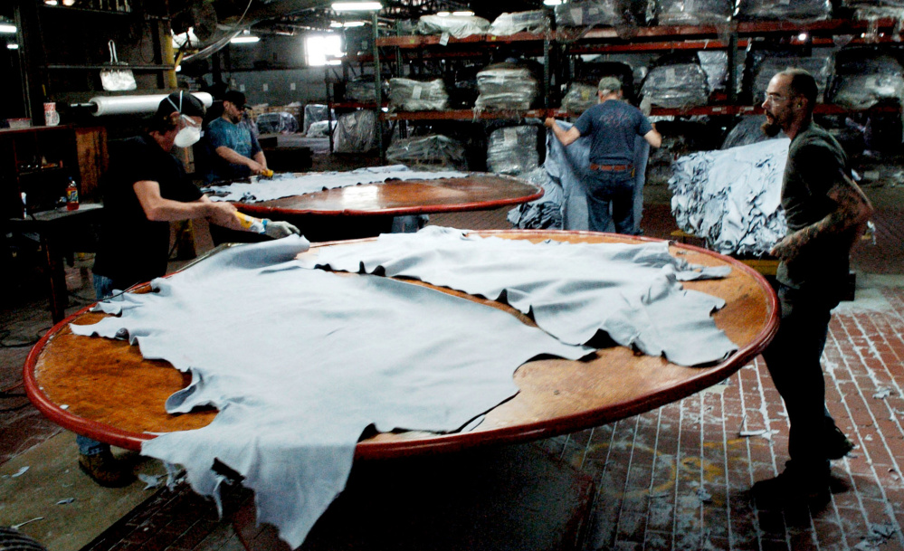 Employees at Tasman Leather work at a station at the Hartland tannery in 2016. Today's guest columnist argues that the impact of globalization on industries such as tanning means that Maine's rural people often have more in common with immigrants from poor regions than they do with owners of the corporate chain stores where they shop.