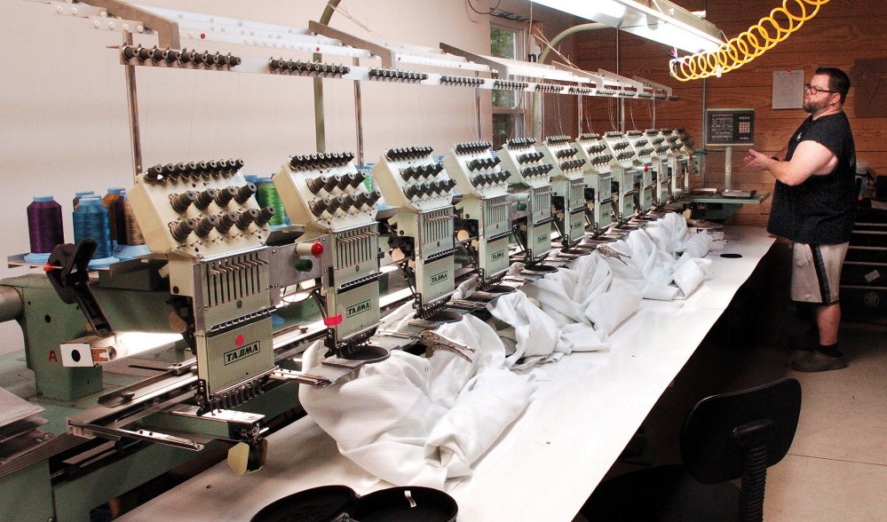 OriginUSA employee Greg Hazard prepares to embroider garments at the facility in Industry.