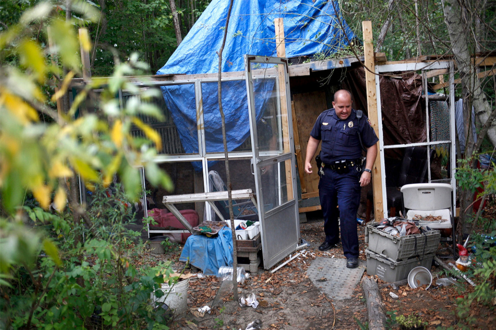Community policing Sgt. Andrew Hutchings makes rounds Wednesday at the homeless encampment on the outskirts of Portland, where he gave remaining occupants one more day to move out.