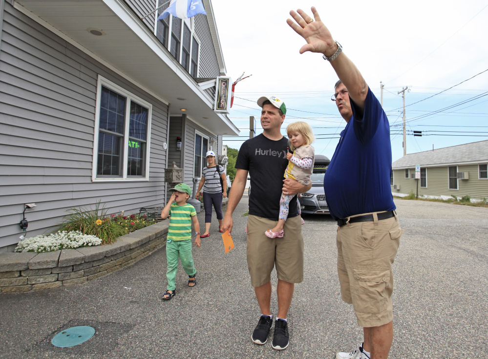 """Mike Bouffard, owner of the Normandie Inn in Old Orchard Beach, points out a room location while helping the Adam family from Quebec check in Monday morning. The family had been motel-hopping since Wednesday as prices and availability fluctuated over the holiday weekend. Labor Day weekend capped an extra busy season for Bouffard. He said, """"The Canadians took it on the chin with the exchange rate,"""" but good weather kept motels full."""