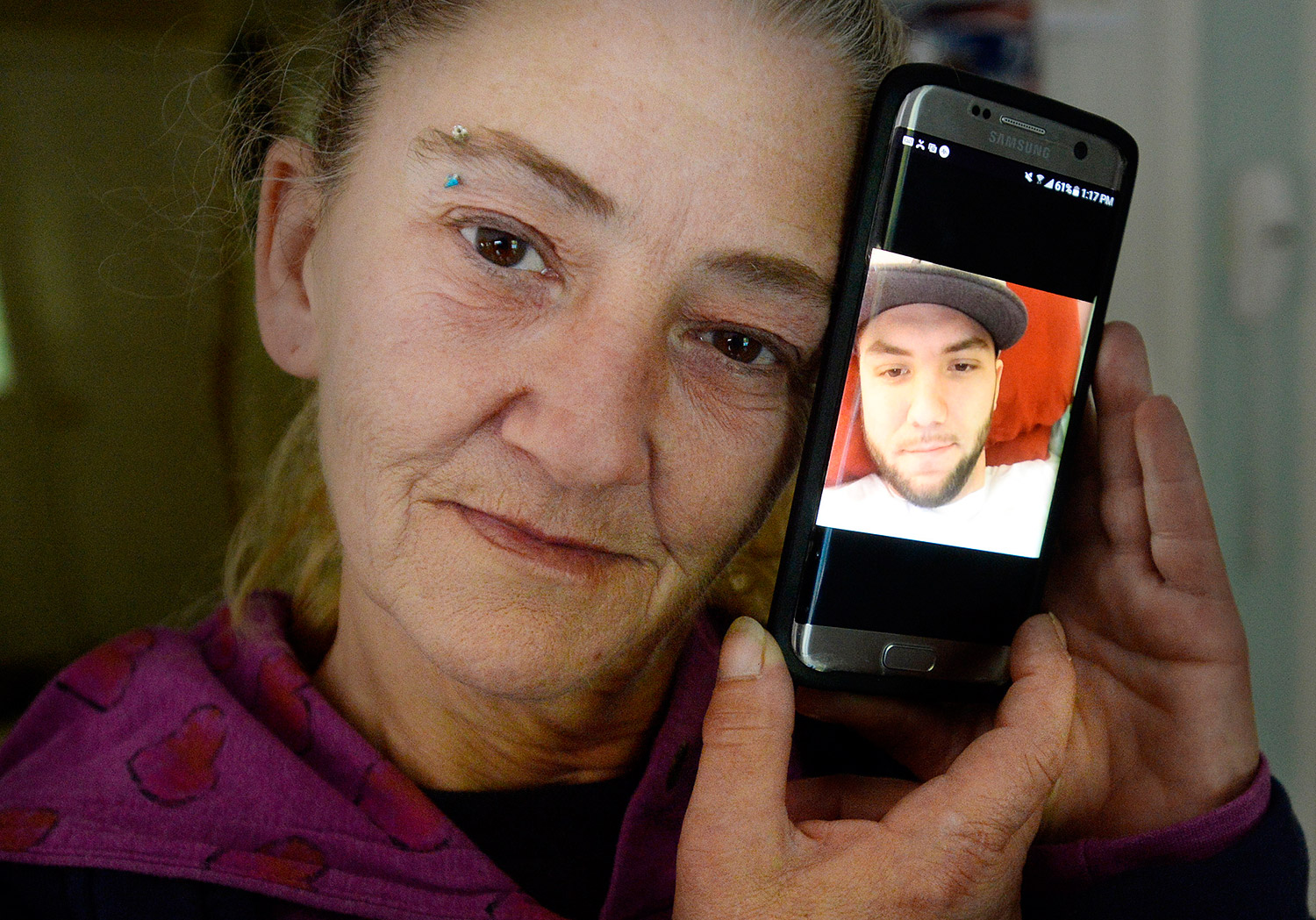 "Cheryl Methot, the mother of Jonathon Methot, who was shot early Monday morning in Biddeford, holds a phone with a photo of her son Friday. She said her son had struggled with prescription opiate addiction, but was working to get his life back on track, and ""was doing really good."" Shawn Patrick Ouellette/Staff Photographer"