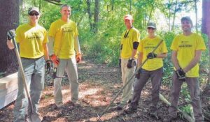 VOLUNTEERS from Stantec work on the waterfront trail in Topsham earlier this summer.