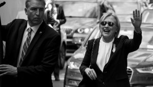 """DEMOCRATIC PRESIDENTIAL CANDIDATE HILLARY CLINTON waves as she walks from her daughter's apartment building Sunda in New York. Clinton unexpectedly left Sunday's 9/11 anniversary ceremony in New York after feeling """"overheated,"""" according to her campaign."""