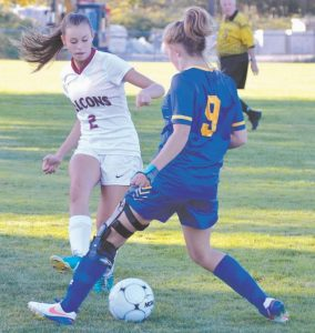 TAYLOR RINALDI (2) of Freeport looks to strike the ball past Falmouth's Cali Wiberg near the touch-line.
