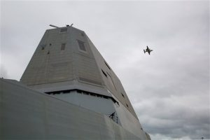 In a Wednesday, Sept.16, 2016 photo, An E-2 Hawkeye flies past the odd-shaped tower of the USS Zumwalt, the Navy's latest destroyer at Norfolk Naval Station in Norfolk, Va. The Navy's newest destroyer will remain in Virginia at Naval Station Norfolk longer than expected after crew members detected a leak on the vessel on Monday, Sept. 19. The ship will stay in Norfolk for repairs before it heads to Baltimore to be commissioned on Oct. 15. It will then sail to its new home in San Diego. (Hyunsoo Léo Kim/The Virginian-Pilot via AP)