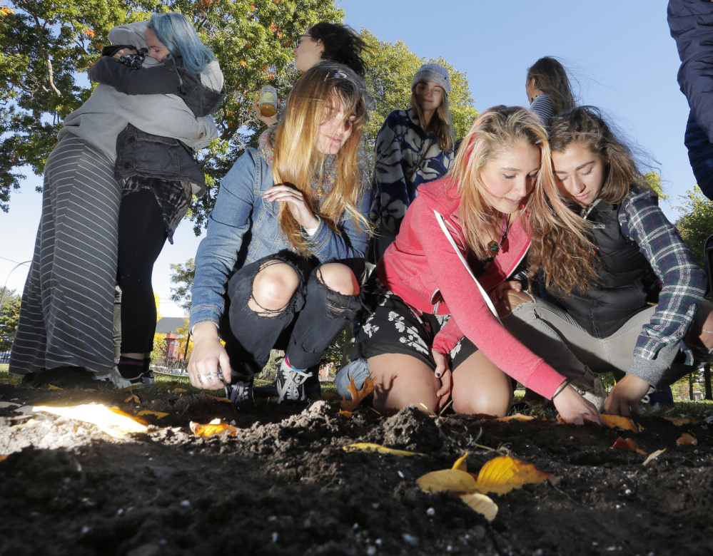 Rosalie Turner, left, and Amelia Bertaska, right, help Julia Hansen plant bulbs in Lincoln Park in Portland Monday. After losing two of her best friends to suicide earlier this year, Hansen, a junior at Casco Bay High School, started The Yellow Tulip Project to raise awareness of mental illness. The bulb planting on Monday coincided with World Mental Health Awareness Day. Turner is a junior at Casco Bay High School and Bertaska is a junior at Waynflete.