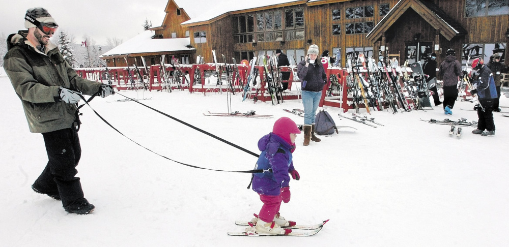 Staff file photo by David Leaming   MUSH: Gabbie Archibald is held by a tether line by her father Ian while skiing for the first time near the renovated baselodge at Saddleback Mtn. ski resort near Rangeley.