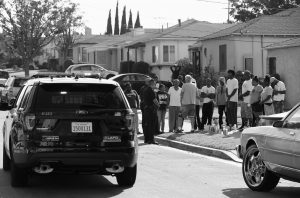 LOS ANGELES POLICE OFFICERS stop their patrol vehicle to speak to neighbors and members of the community gathered around a makeshift memorial outside a residence on Sunday. Officers shot and killed Carnell Snell Jr. in south Los Angeles on Saturday at the end of a car chase, sparking a protest by several dozen people angered by another fatal police shooting of a black man.