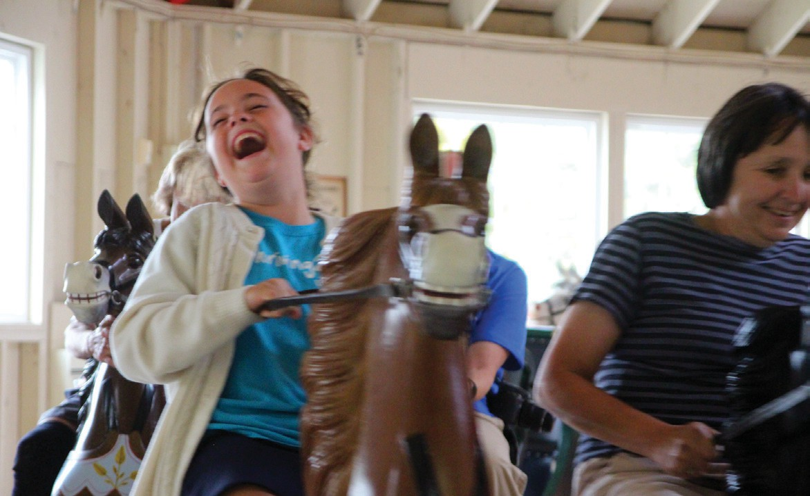Right: Ayerabella, left, and Diane Harrington of Cornish enjoy the ride October 8 on the 1894 Armitage Herschell carousel at 19th Century Willowbrook Village in Newfield. Its properties and collections will be gifted to several historical nonprofits, the majority to The Curran Homestead in Orrington. Below: Michelle Sherman of Springvale tries her hand at pumping water the old-fashioned way on Willowbrook's last day.