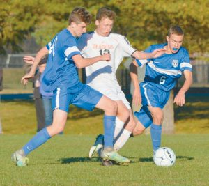 BRUNSWICK AND MT. ARARAT battled it out in a KVAC boys soccer clash in Brunswick on Tuesday. The Eagles won, 2-1 in double overtime. In the photos, clockwise from the top of the page, Brunswick's Emmet Taub, center, battles with Mt. Ararat's Kyle Brown (20) and Max Spelke (6); Eagle Travis Nadeau controls the ball; the ball bounds between Dragons Jared Hummer, center, and Noah Greene (21) with Nadeau close by; and Dragon Carlyle Boyle (4) battles with Mt. Ararat's James Hutchinson.