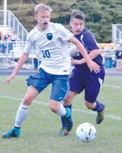 HAMPDEN ACADEMY'S Alex Ross, right, pressures Mt. Ararat's Kyle Brown (20) during a boys high school soccer KVAC contest in Topsham on Tuesday. The Eagles won their ninth straight with a 4-0 victory over the 3-7 Broncos.