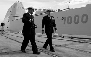LT. RICK MOORE, left, and Capt. James Kirk, commanding officer of the USS Zumwalt, walk past the ship to a news conference in Baltimore. Designed and built with an angular shape to minimize its radar signature, it's the most expensive destroyer ever built for the Navy.