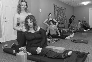 JENNIFER DAVIS of Framingham, Massachusetts, left, participates in an adaptive yoga class for people with disabilities and mobility impairment at Roots and Wings in Natick. Assisting her is Radha Hutchinson.