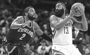 HOUSTON ROCKETS guard James Harden looks to pass to a teammate as Cleveland Cavaliers guard Kyrie Irving (2) defends in the second half of an NBA basketball game on Tuesday in Cleveland. The Cavaliers won, 128-120.