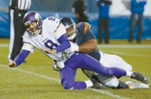 CHICAGO BEARS defensive end Cornelius Washington (90) pressures Minnesota Vikings quarterback Sam Bradford (8) after a throw during the second half of an NFL football game in Chicago on Monday. The Bears won, 20-10.