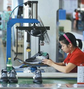 A WORKER ASSEMBLES sneakers at a factory in Jinjiang city in southeast China's Fujian province.