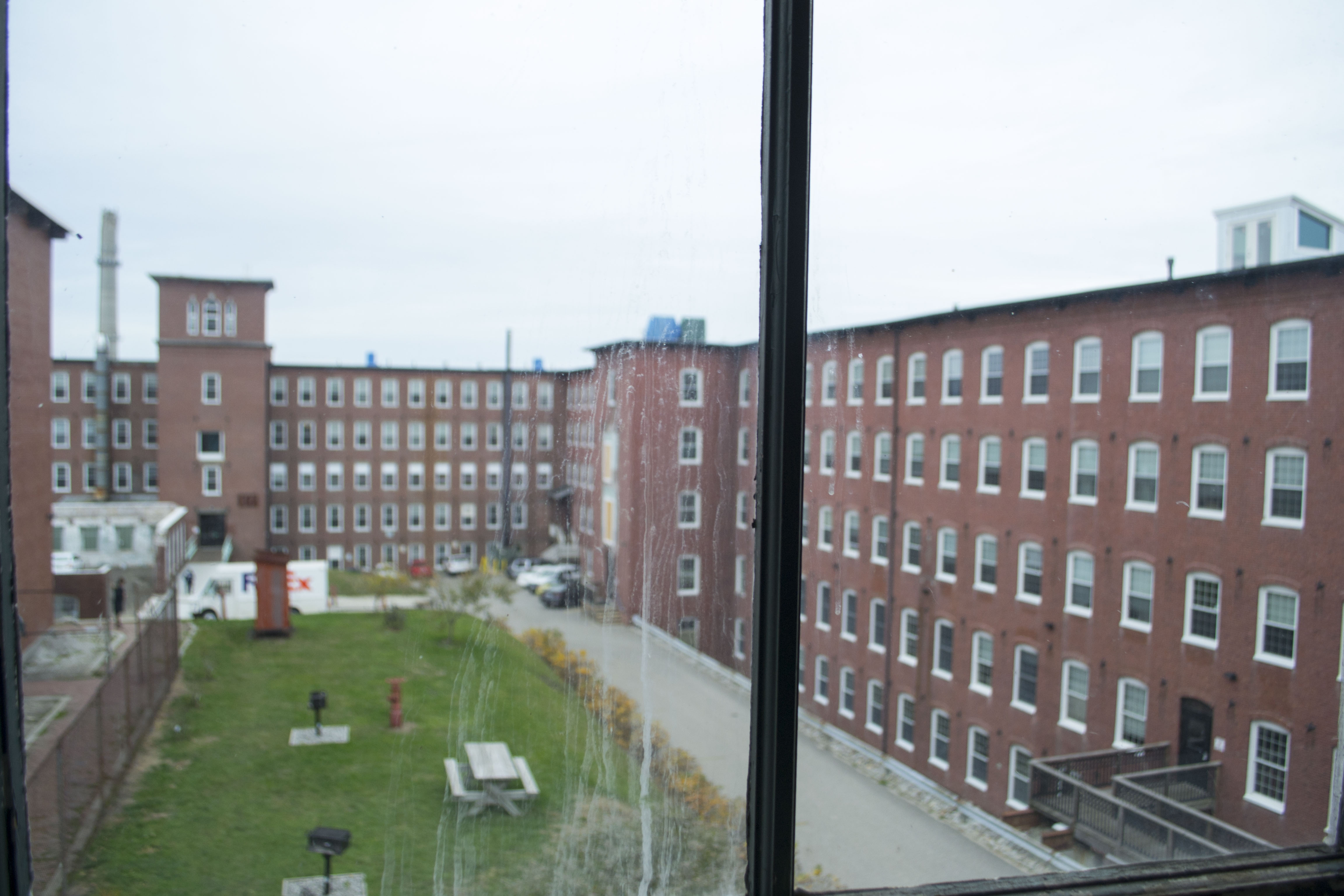 """Buildings 17 and 18 of the North Dam Mill complex can be seen from the window of a former office space in the Pepperell Mill. Guillerault said he expects the Pepperell space to change as those spaces have, into offices, restaurants and housing —a change he welcomes with open arms. """"It's given new life and a renewed sense of purpose"""" to the mills, he said. ALAN BENNETT/Journal Tribune"""