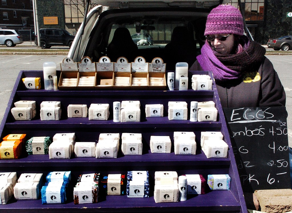 Joanne Gorey sets out soaps from her A Page N Thyme Farm and Soap shop at the downtown Waterville farmers market. Many of Maine's soapmakers use ingredients from their farms to make their soaps.