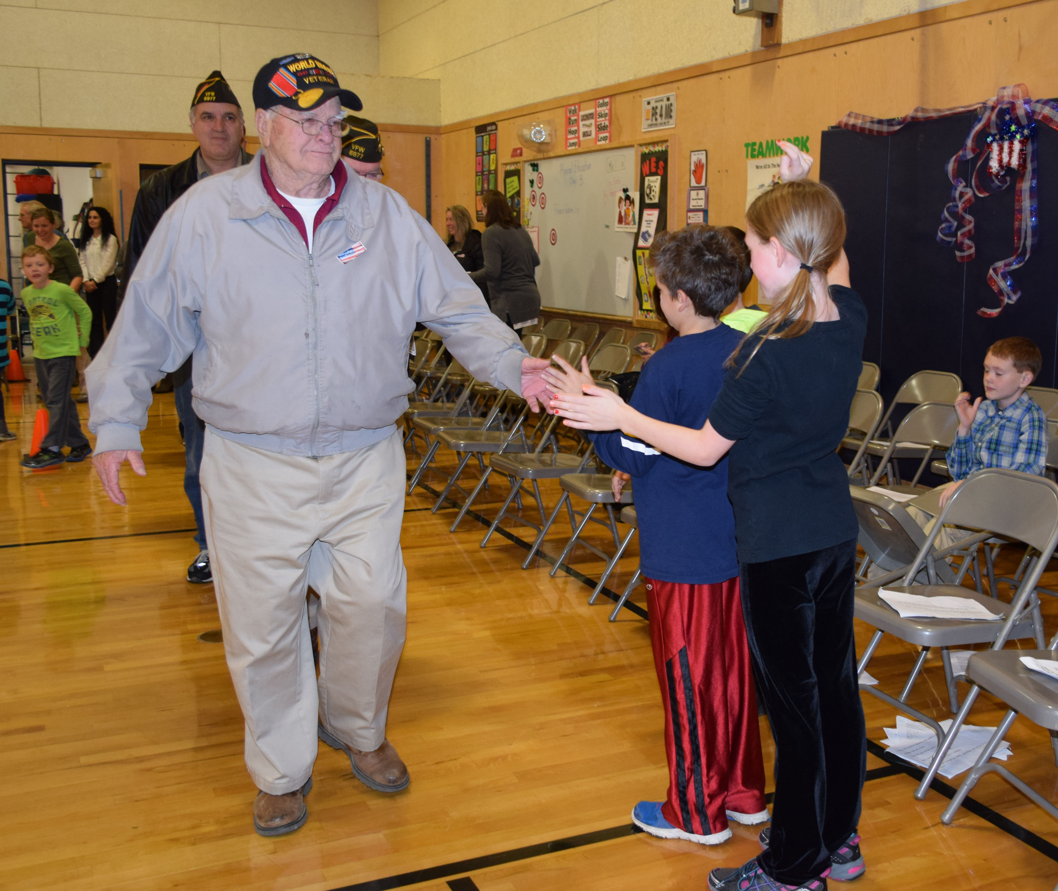 At the end of the Veterans Day assembly at Wells Elementary students lined up to shake hands with the guest veterans. World War II Veteran John Primerano greets students at the end of K-4 assembly Nov. 10. Behind Primerano is Roger LaPlante, a U.S. Air Force veteran.