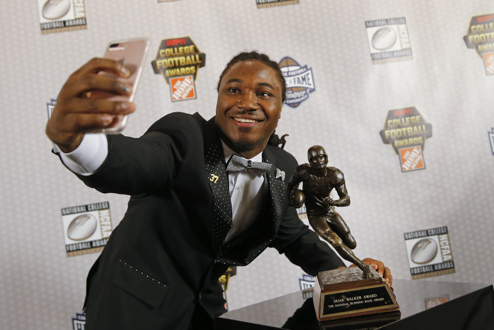 Texas running back D'Onta Foreman takes a selfie with the Doak Walker Award on Thursday after winning it for being the nation's premier running back. Foreman has rushed for 2,028 yards this season.