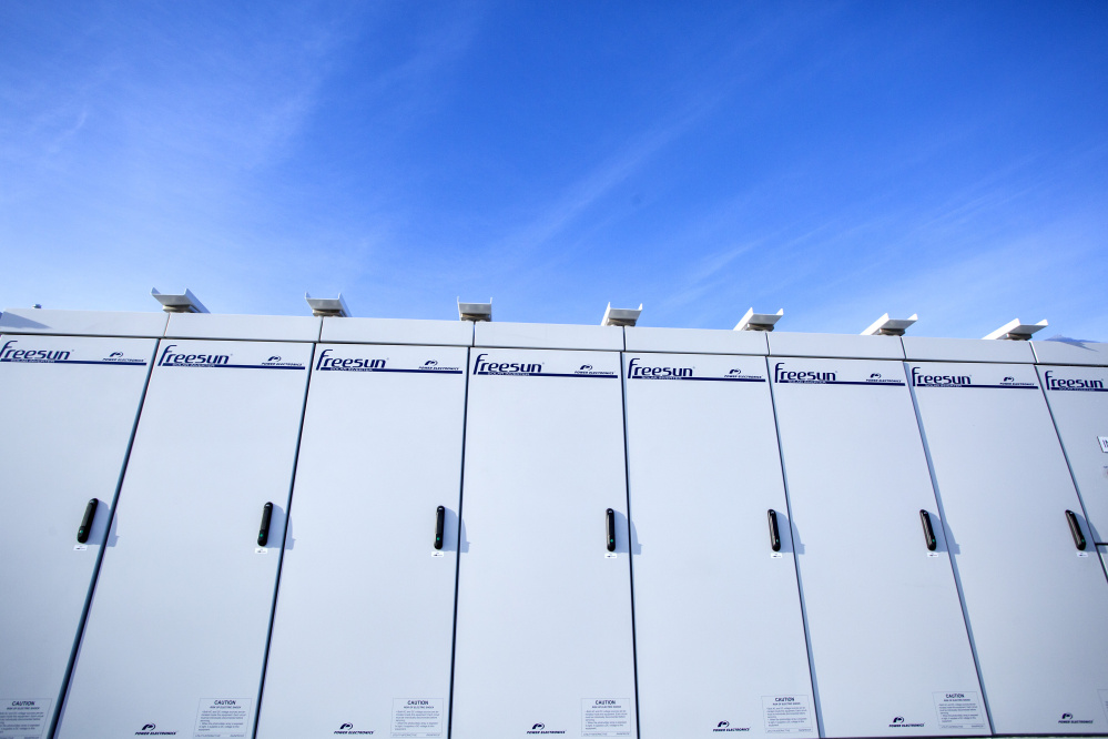 Inside a warehouse at Wyman Station, eight metal cabinets hold the battery. Outside, this bank of inverters converts the power to alternating current.