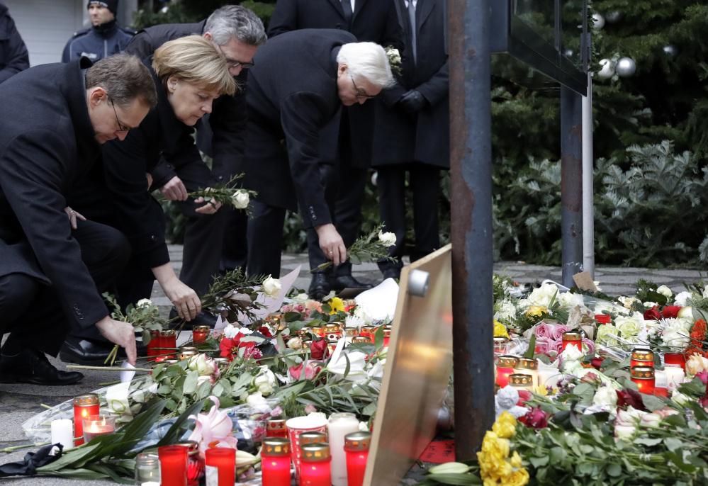 From left, Berlin Mayor Michael Mueller, Chancellor Angela Merkel, Interior Minister Thomas de Maiziere and Foreign Minister Frank-Walter Steinmeier attend a flower ceremony at the Kaiser-Wilhelm-Gedaechniskirche in Berlin on Tuesday, the day after a truck ran into a crowded Christmas market and killed 12 people.