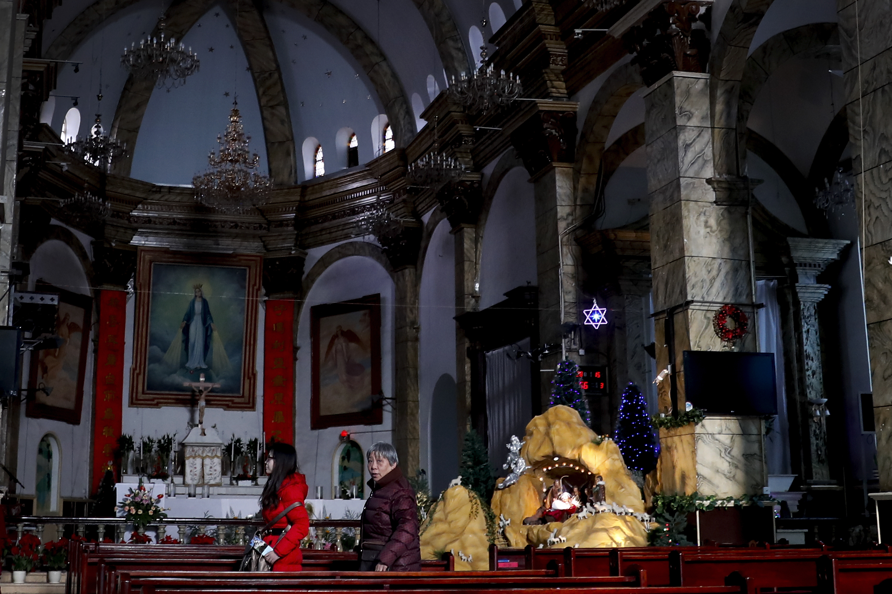 """In this Wednesday photo, Chinese women walk past a decoration displaying a Baby Jesus doll part of a Nativity scene, at the Nantang Catholic Church in Beijing. One of China's top leaders told Chinese Catholics that they need to operate """"independently"""" of outside forces and promote socialism and patriotism through religion. AP WIREPHOTO"""