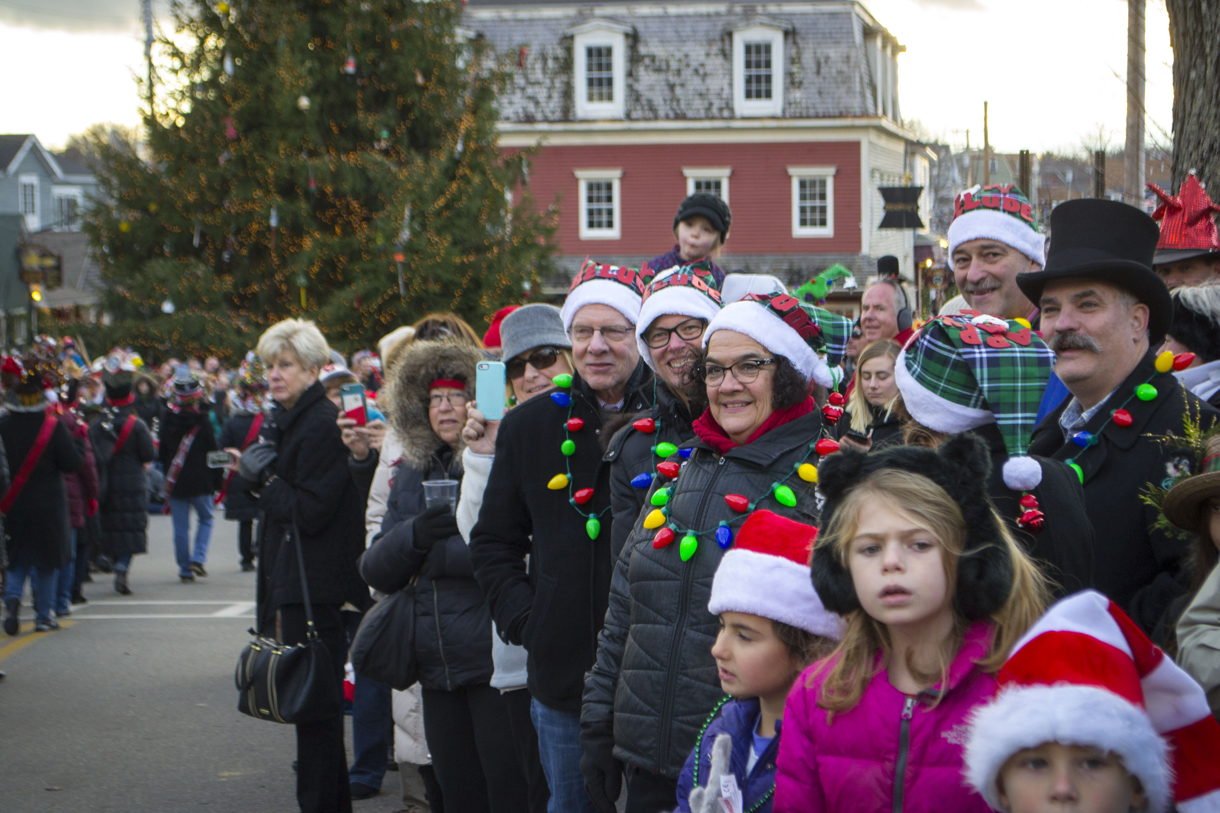 ALAN BENNETT/Journal Tribune. Spectators, hundreds of them, watch as the Hat Parade moves through Kennebunkport's Dock Square during Christmas Prelude on Saturday.