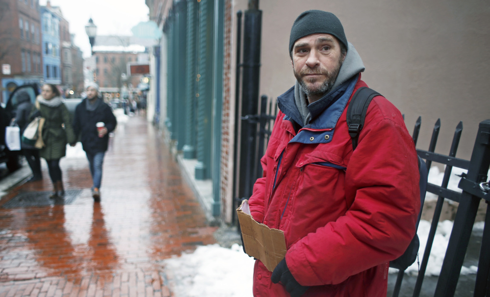 Edward Lane panhandles Tuesday on Exchange Street in Portland. A business group hoping to curb the practice plans to research how other communities are addressing the issue.
