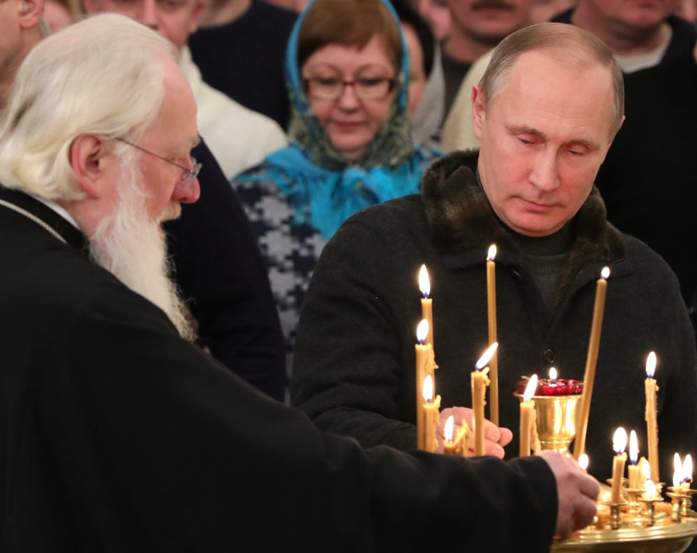 Russian President Vladimir Putin lights a candle prior to a midnight Orthodox Christmas Mass at the St. George's Monastery, Novgorod Region, about 300 miles northwest of Moscow, on Friday. Orthodox Christians celebrate Christmas on Jan. 7, in accordance with the Julian calendar.