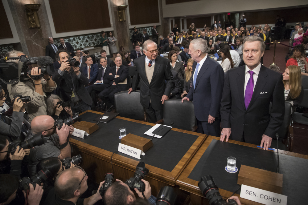 Defense Secretary-designate James Mattis, center, flanked by former Georgia Sen. Sam Nunn, left, and former Maine Sen. and former Defense Secretary William Cohen, arrives on Capitol Hill in Washington on Thursday to testify at his confirmation hearing before the Senate Armed Services Committee.