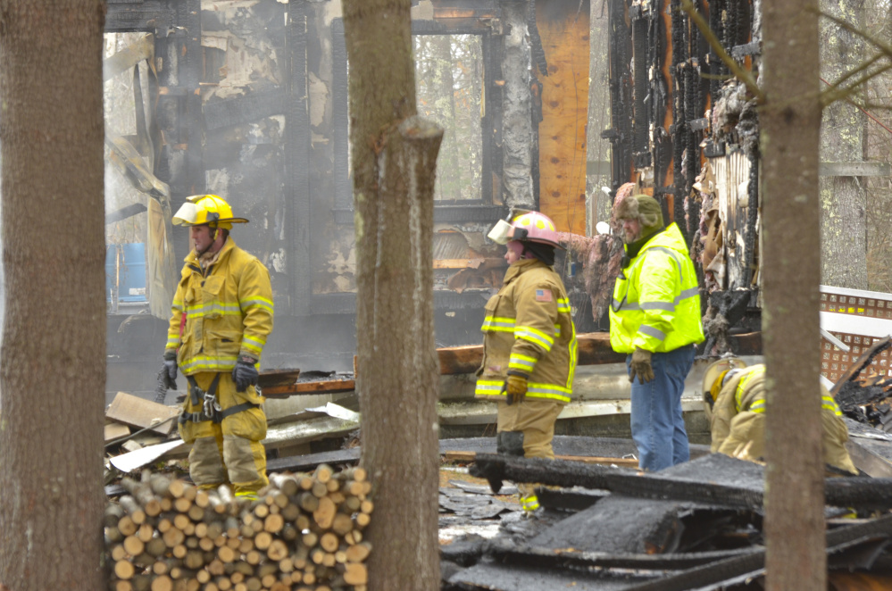 Firefighters walk through remnants of the house that was destroyed Monday in an early morning fire that left two dead in the town of Washington.