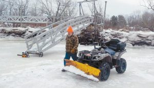 JIM MCPHERSON of Jim's Camps in Bowdoinham prepares the ice for his smelt shacks earlier this month.