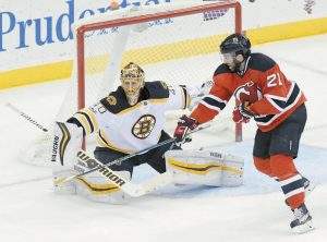 NEW JERSEY DEVILS' Kyle Palmieri, right, attempts to deflect the puck as Boston Bruins goaltender Tuukka Risk makes a save during the second period of an NHL hockey game on Monday in Newark, N.J.