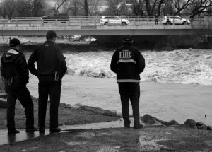 SPARKS FIREFIGHTERS monitor the rising Truckee River Sunday where it runs near the Grand Sierra hotel-casino along a line that divides the cities of Reno and Sparks, Nevada. More than 1,000 homes have been evacuated due to overflowing streams and drainage ditches in the area, which remains under a flood warning through Tuesday.