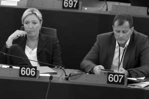 """FRENCH FAR RIGHT LEADER MARINE LE PEN, left, and party vice-president Louis Aliot listen to debates at the European Parliament in Strasbourg, eastern France in 2014. Money, and how to get it, has dogged French far-right presidential contender Marine Le Pen for years. Now, as her National Front party's treasurer says it's looking """"everywhere"""" for the $21 million) needed to fund upcoming campaigns, she may be looking to Russia for cash again."""