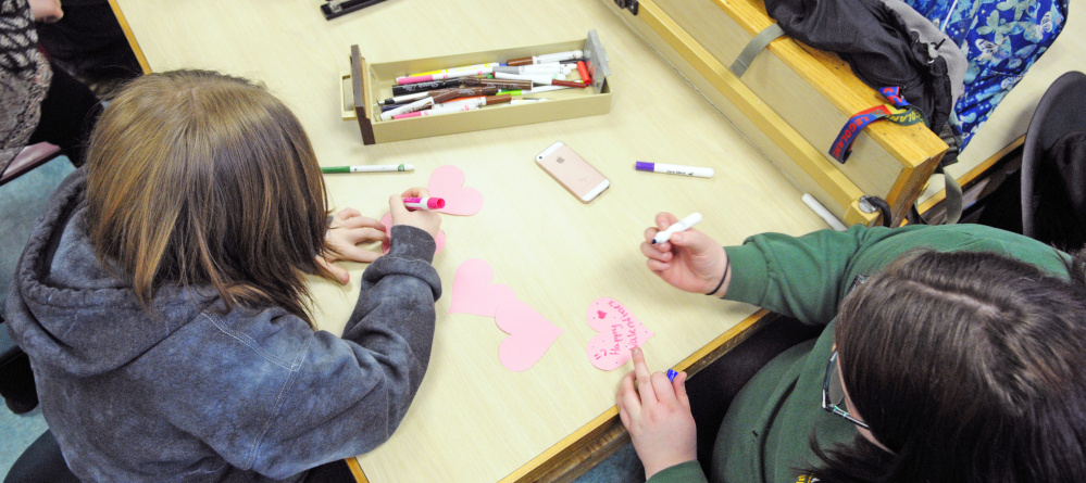 Morgan Ross, left, and Rose Fendley make Valentine's Day cards to be distributed at the Maine Veterans' Home in Augusta during a Jobs for Maine's Graduates class Friday at Hall-Dale High School in Farmingdale.