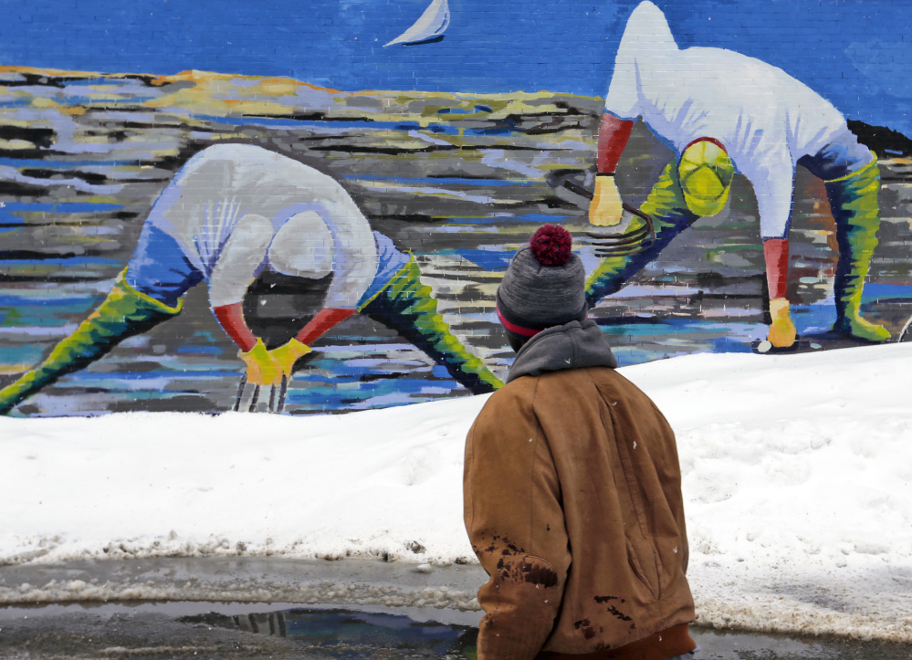 Above, clammers appear to be digging in fresh snow piles in artist Susan Bartlett Rice's mural as Larry Mundu of Portland navigates the streets. At top, a Kennebunk stop sign coated in heavy wet snow carries a double meaning Thursday morning as Mainers dug out for the third time in a week.