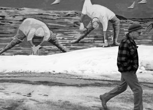 CLAMMERS APPEAR TO BE DIGGING in snow piles in artist Susan Bartlett Rice's mural as Portland resident Joe Downs walks past in Portland Thursday, in the above photo by Ben McCanna. On the right, a car drives our from under a birch tree bowed over under the weight of wet snow in Kennebunk in this photo by Gregory Rec.