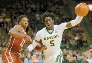 OKLAHOMA'S Kristian Doolittle (11) defends as Baylor's Mark Vital (11) positions for a shot opportunity in the second half of an NCAA college basketball game on Tuesday in Waco, Texas.