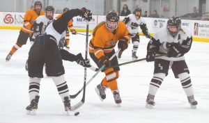 BRUNSWICK FORWARD Beth Labbe, center, cuts between St. Dom's defenders Isabel Frenette (left) and Katya Dons during a girls North regional semifinal at Norway Savings Banks Arena in Auburn on Tuesday. Labbe scored a goal, but the fifth-seeded Dragons fell to the No. 1 Saints, 6-2.