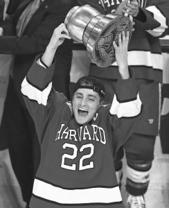 HARVARD FORWARD Devin Tringale hoists the Beanpot trophy after a 6-3 victory over Boston University at the Beanpot college hockey tournament in Boston on Monday.