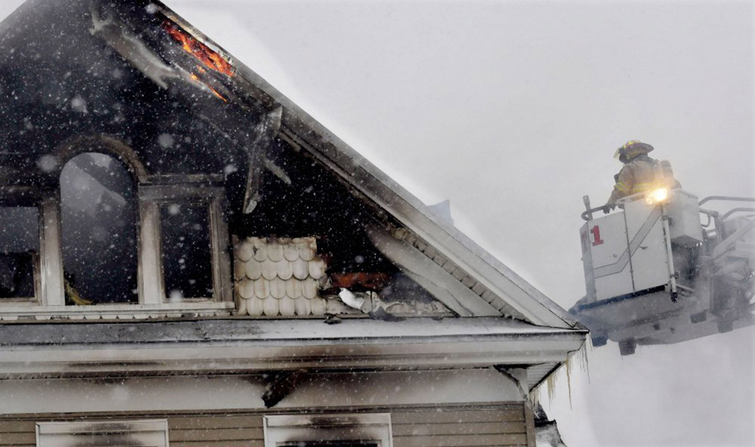 Fire can be seen in an eave as firefighters battle a fire from atop a ladder at an apartment building on Summer Street in Waterville early Wednesday morning.