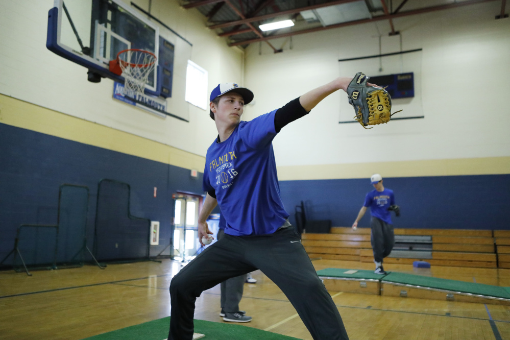Falmouth High School's Max Fortier winds up for a pitch during the first baseball practice of the season Monday. The new rules on pitch counts are likely to force teams to carry more pitchers.