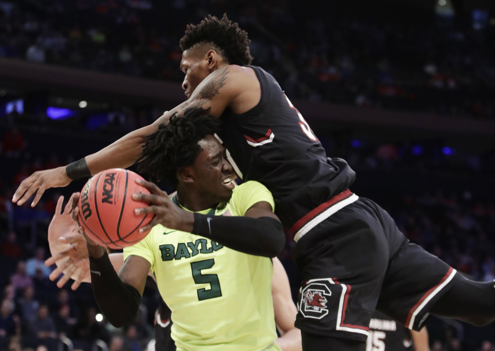 Baylor forward Johnathan Motley, left, looks to pass against South Carolina forward Chris Silva during the first half of South Carolina's 70-50 win Friday in New York.