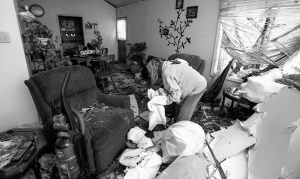 """DEBBIE LOUGHRIDGE is seen going through rubble in her living room in Naplate, Ill., Wednesday, March 1. She rode out the storm in the bathtub. """"All I heard was the wind and the breaking glass. Like an explosion of glass,"""" Loughridge said."""