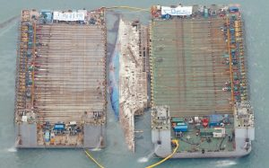 WORKERS TRY TO RAISE the sunken Sewol ferry between two barges during the salvage operation in waters off Jindo, South Korea, today. The 6,800-ton South Korean ferry emerged from the water today, nearly three years after it capsized and sank into violent seas off the country's southwestern coast, an emotional moment for the country that continues to search for closure to one of its deadliest disasters ever.